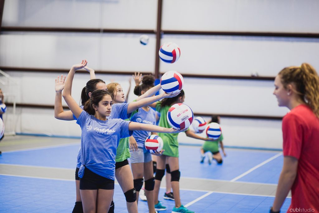 group of girls practicing hitting a volleyball